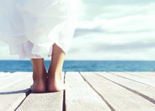 Beautiful legs of a young woman in white skirt on a wooden pier stock photography