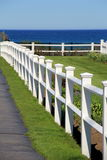 Beautiful length of white fencing leading to the seashore Stock Photography