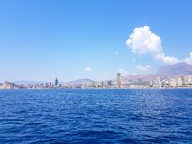 Beautiful Levante beach in Benidorm, Spain. Image taken from the sea, with the skyline of skyscrapers and a boat of first motive. Concept of holidays in stock photos