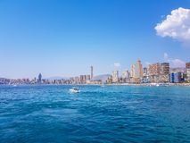 Beautiful Levante beach in Benidorm, Spain. Image taken from the sea, with the skyline of skyscrapers and a boat of first motive. Concept of holidays in stock photography