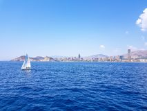 Beautiful Levante beach in Benidorm, Spain. Image taken from the sea, with the skyline of skyscrapers and a boat of first motive. Concept of holidays in royalty free stock images