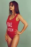 Beautiful lifeguard wearing a red swimwear. Beautiful lifeguard posing over a green background Stock Photography