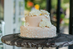 Beautiful light pink and tasty wedding cake. Cake decorated with flowers from marzipan on the table Royalty Free Stock Photo