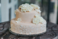 Beautiful light pink and tasty wedding cake. Cake decorated with flowers from marzipan on the table Royalty Free Stock Photos
