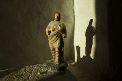 Beautiful light shining on Jesus statue. Inside small chapel and church in Razanj Croatia Europe. Old religious stone house building. Open door with light Stock Photography