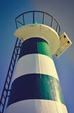 Beautiful lighthouse with bright sun on top on sky Stock Photography