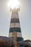 Beautiful lighthouse with bright sun on top on sky Stock Photos
