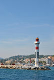 Beautiful lighthouse on the stone pier and cityscape at back, port of Marseille, France Royalty Free Stock Photos