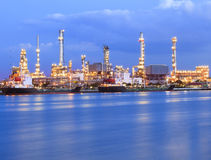 Beautiful lighting of oil refinery industry plant beside blue river use for energy industrial business theme