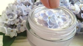 Beautiful lilac bouquet cluster botany ccosmetic cream. Beautiful lilac bouquet cosmetic cream white wooden background