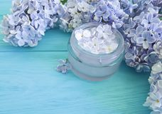 Beautiful lilac flower cosmetic therapy harmonymoisturizer container cream on a blue wooden background. Beautiful lilac flower cosmetic cream container a blue stock photos