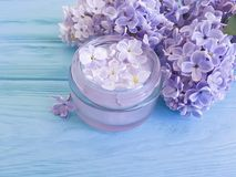 Beautiful lilac flower violet cosmetic therapy container cream on a blue wooden background. Beautiful lilac flower cosmetic cream violet container a blue wooden stock images