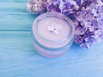 Beautiful lilac flower violet homemade therapy container cream on a blue wooden background. Beautiful lilac flower cosmetic cream violet container a blue wooden royalty free stock photography