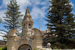 Beautiful limestone archway in front of Naxxar parish church, viewed from Palazzo Parisio, Naxxar, Malta, Europe.  June 2016. Blue skies and fir trees Royalty Free Stock Images