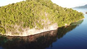 Aerial View of Rock Island and Calm Water in Raja Ampat. A beautiful limestone island, surrounded by calm waters and coral reefs, is found in Raja Ampat stock footage