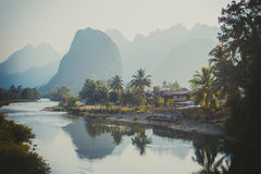 Beautiful limestone mountains reflected in a river. Limestone hills in haze reflected in a river, near Vang Vieng, Laos Royalty Free Stock Photo