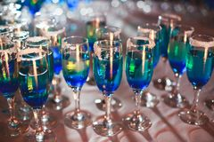 Beautiful line of different colored alcohol cocktails with smoke on a Christmas party, tequila, martini, vodka, and others on part. Beautiful line of different Royalty Free Stock Images