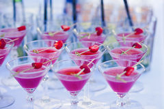 Beautiful line of different colored alcohol cocktails with smoke on a Christmas party, tequila, martini, vodka, and others on part Royalty Free Stock Photography