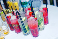 Beautiful line of different colored alcohol cocktails with smoke on a Christmas party, tequila, martini, vodka, and others on part. Beautiful line of different Stock Photo