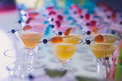 Beautiful line of different colored alcohol cocktails with smoke on a Christmas party, tequila, martini, vodka, and others on part stock photo