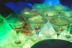 Beautiful line of different colored alcohol cocktails with smoke on a Christmas party, tequila, martini, vodka, and others on part Royalty Free Stock Images