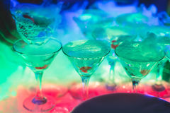 Beautiful line of different colored alcohol cocktails with smoke on a Christmas party, tequila, martini, vodka, and others on part Stock Images