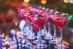 Beautiful line of different colored alcohol cocktails with smoke on a Christmas party, tequila, martini, vodka, and others on part. Beautiful line of different Stock Photos