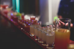 Beautiful line of different colored alcohol cocktails, tequila, martini, vodka, and others on decorated catering banquet table Royalty Free Stock Photo