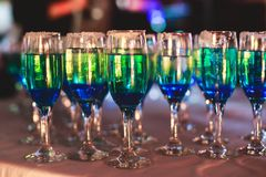 Beautiful line of different colored alcohol cocktails with smoke on a Christmas party, tequila, martini, vodka, and others on part Stock Photos
