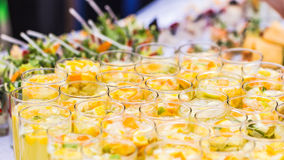 Beautiful line of different coloured cocktails on a open air party, catering table stock photography