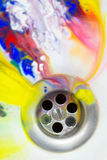 Beautiful liquid paint flowing down the drain as bright colorful Stock Photos