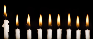 Beautiful lit hanukkah candles on black. Stock Photos
