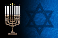 Beautiful lit hanukkah menorah. Artisanall lit hanukkah menorah and David' star on black background