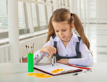 Beautiful litle schoolgirl siiting at table Stock Photos