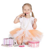 Beautiful litlle girl puts makeup over white Royalty Free Stock Images