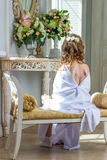 Beautiful little angel with wings sitting and thinking Royalty Free Stock Image