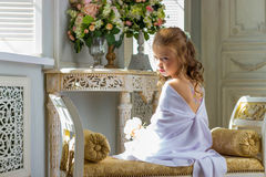 Beautiful little angel with wings sitting and thinking Royalty Free Stock Photos