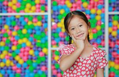 Beautiful little Asian child girl holding index finger on cheek against colorful toy ball playground.  stock photos