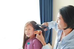 Beautiful little Asian child girl with long hair and mom dressed up for Smooth hair at morning in the room royalty free stock images
