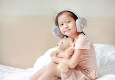 Beautiful little Asian child girl wearing winter earmuffs with looking camera and embracing teddy bear while sitting on the bed at stock images