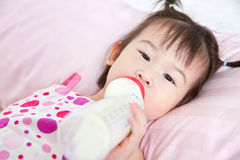 Beautiful little asian girl lying and suck up milk Stock Image