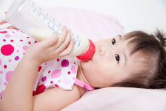 Beautiful little asian girl lying and suck up milk Stock Photos