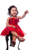 Little girl in red dress. Beautiful little asian girl in a red dress sitting on a chair, laughing and reaching out Royalty Free Stock Photos