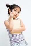 Beautiful little Asian girl thinking with pencil and notebook Stock Photos