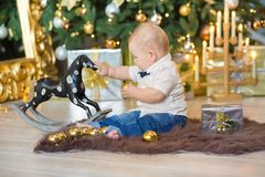 Beautiful little baby boy celebrates Christmas. New Year`s holidays. Baby in a Christmas costume casual clothes with gifts on fur Stock Photo