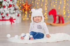 Beautiful little baby boy celebrates Christmas. New Year`s holidays. Baby in a Christmas costume casual clothes with gifts on fur Royalty Free Stock Photos