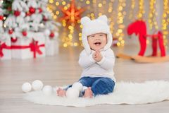 Beautiful little baby boy celebrates Christmas. New Year`s holidays. Baby in a Christmas costume casual clothes with gifts on fur Stock Image