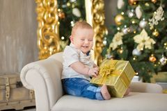 Beautiful little baby boy celebrates Christmas. New Year`s holidays. Baby in a Christmas costume casual clothes with gifts on fur Stock Photos