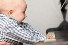 Beautiful little baby boy plays piano Stock Photos