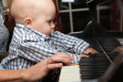 Beautiful little baby boy plays piano Royalty Free Stock Photo